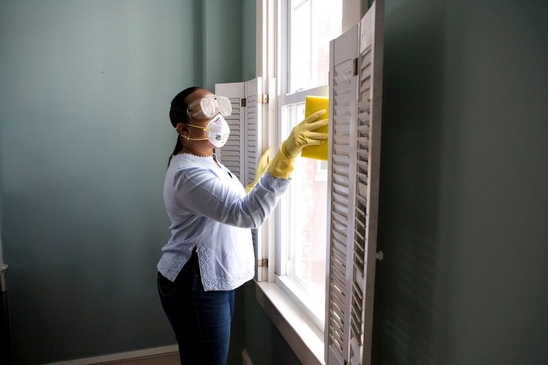 A woman cleaning the windows.